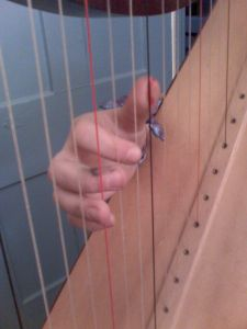 A hand playing harp strings