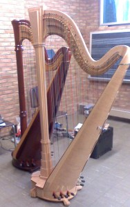 Two orchestral harps standing side by side