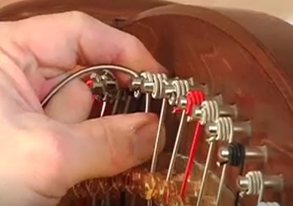 Keep your fingers on the wire to help guide it into a coil as you turn the tuning pin.